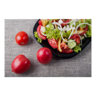 Fresh tomatoes and a part of a plate with salad poster