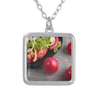 Fresh tomatoes and a part of a plate with salad silver plated necklace