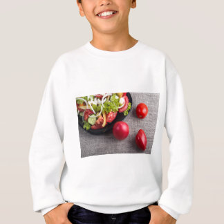 Fresh tomatoes and a part of a plate with salad sweatshirt