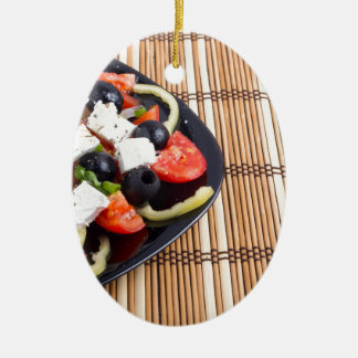Fresh vegetarian salad in a black plate on a mat ceramic oval decoration