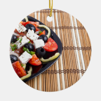Fresh vegetarian salad in a black plate on a mat round ceramic decoration