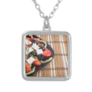 Fresh vegetarian salad in a black plate on a mat silver plated necklace