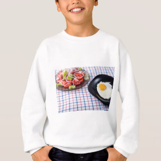 Fried egg with the yolk and tomato salad on fabric sweatshirt