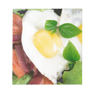 Fried eggs and bacon with herbs and lettuce notepad