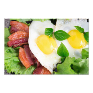 Fried eggs and bacon with herbs and lettuce photo art