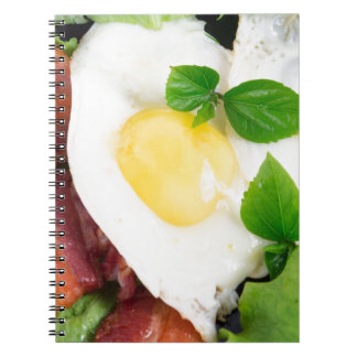 Fried eggs and bacon with herbs and lettuce spiral notebook