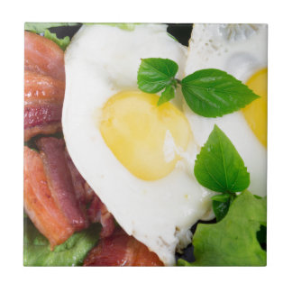 Fried eggs and bacon with herbs and lettuce tile