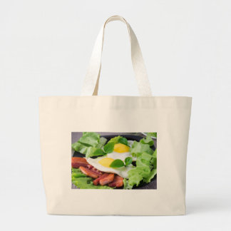 Fried eggs with herbs, lettuce and  bacon large tote bag