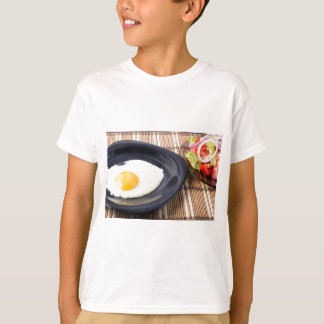 Fried eggs with yolk on a black plate and a salad T-Shirt