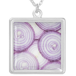 Full frame of sliced red onion, on white square pendant necklace