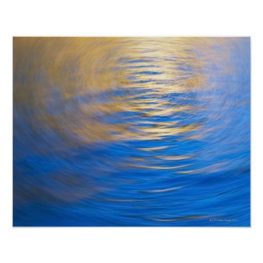 Gently rippled water reflecting gold and blue posters