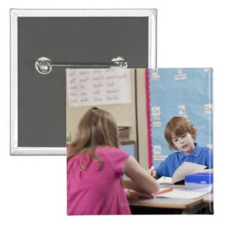 Girl (10-11) and boy (6-7) reading in classroom 15 cm square badge