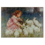 Girl feeding rabbits cutting boards