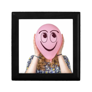 Girl holding pink balloon with smiling face small square gift box