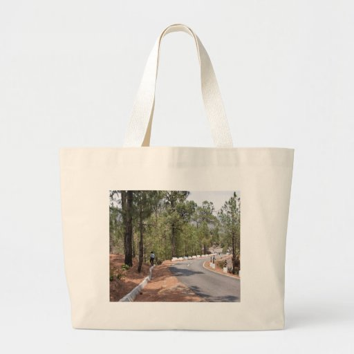 Girl on a mountain highway road tote bags