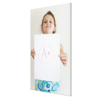 Girl showing off A+ grade on paper Canvas Print