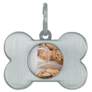 Glass cup with milk and oatmeal cookies pet ID tag