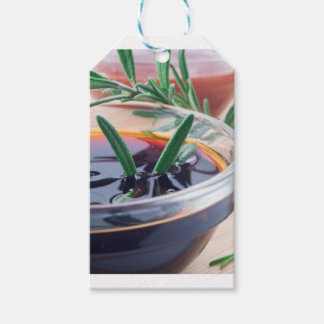 Glass cup with soy sauce and rosemary gift tags