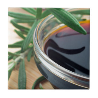 Glass cup with soy sauce and rosemary leaves close tile