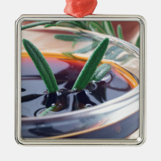 Glass cup with soy sauce and rosemary metal ornament
