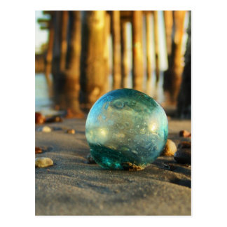 Glass float in front of pier postcard
