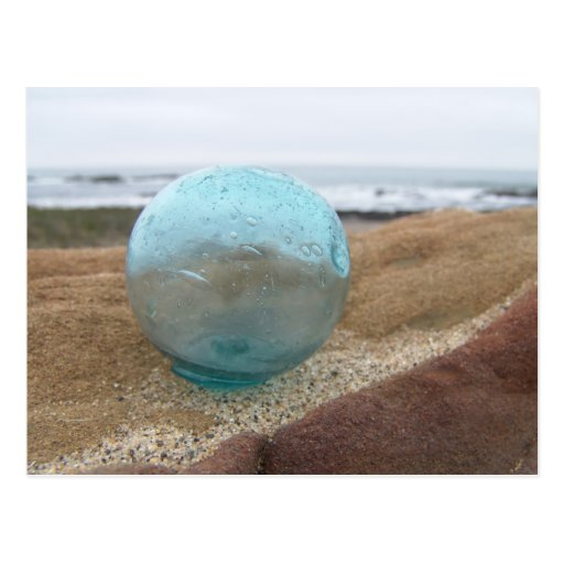Glass float on sand at beach postcard
