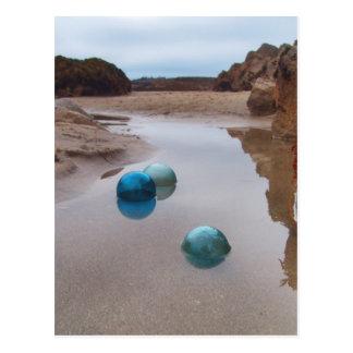 Glass floats on receding water postcard