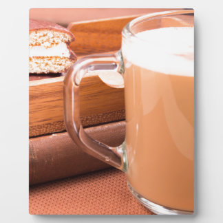 Glass mug with hot chocolate and biscuits plaque