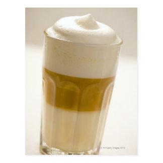 Glass of latte macchiato, close up postcard