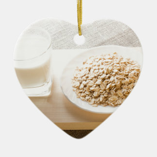 Glass of milk and a plate of cereal closeup ceramic heart decoration