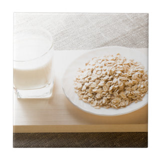 Glass of milk and a plate of cereal closeup ceramic tile