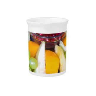 Glass scale full of various fresh fruits pitcher