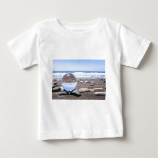 Glass sphere on stones at beach and coast baby T-Shirt