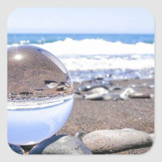 Glass sphere on stones at beach and coast square sticker