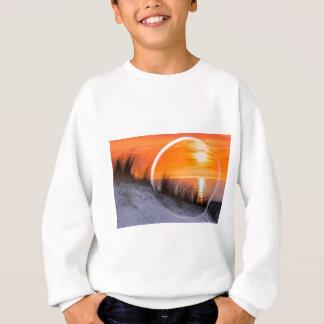Glass sphere reflecting orange sunset sweatshirt
