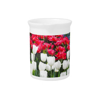 Glass sphere reflecting red white tulips and blue beverage pitchers