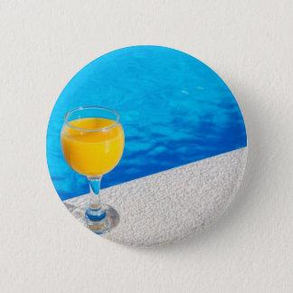 Glass with orange juice on edge of swimming pool 6 cm round badge