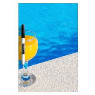 Glass with orange juice on edge of swimming pool dry erase boards