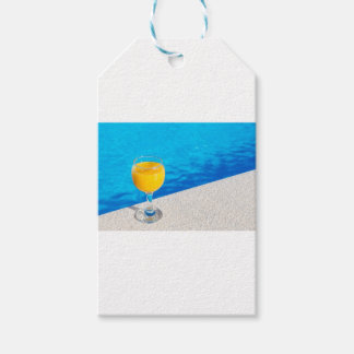 Glass with orange juice on edge of swimming pool gift tags