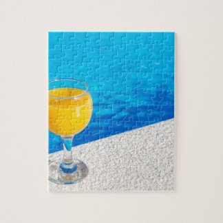 Glass with orange juice on edge of swimming pool jigsaw puzzle
