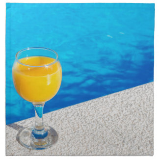 Glass with orange juice on edge of swimming pool napkin