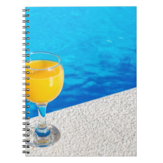 Glass with orange juice on edge of swimming pool notebook