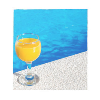 Glass with orange juice on edge of swimming pool notepad