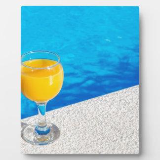 Glass with orange juice on edge of swimming pool plaque