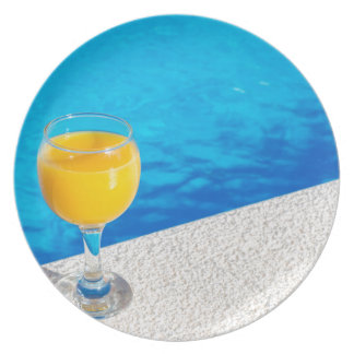 Glass with orange juice on edge of swimming pool plate