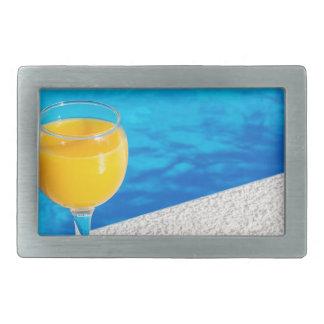Glass with orange juice on edge of swimming pool rectangular belt buckles