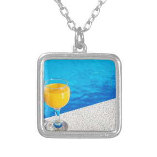 Glass with orange juice on edge of swimming pool silver plated necklace