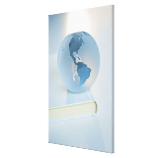Globe on a book stretched canvas print