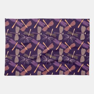 Glowing night dragonflies on dark plum background tea towel