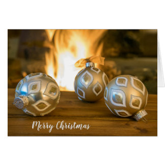 gold Christmas ornaments by fireplace Card